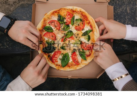 Photo of Top view image of couple grab slices of pizza from box at the outdoor. Man and woman hands taking pizza. Vegan pizza with fresh tomatoes basil and broccoli. Lactose and gluten free