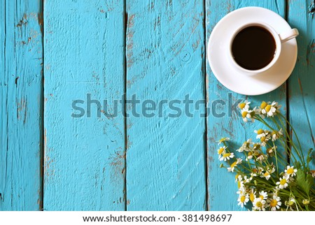 top view image of daisy flowers next to cup of coffee on blue wooden table. vintage filtered and toned