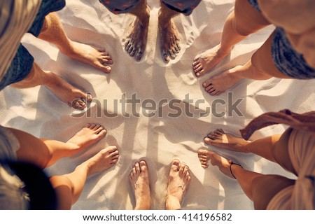 Top view image of feet of young people standing in a circle. Mixed race friends standing barefoot on sandy beach. Concept of unity in diversity.