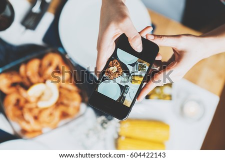 Top view image of female hands taking a picture of homemade food by smartphone, hipster girl making a photo of table with food on cellphone