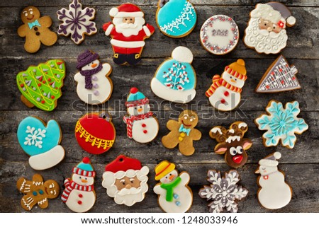 Top view image of festive gingerbread cookies group. Tasty iced christmas bisquits as a New Year decoration at textured woodem background.