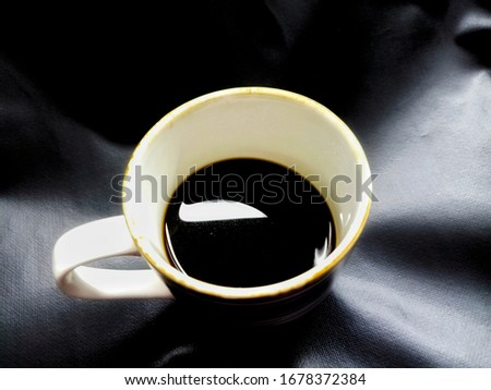 Photo of Top view image of hot black coffee with sugar free in a white ceramic cup isolated on black background with light shadow wrinkles.