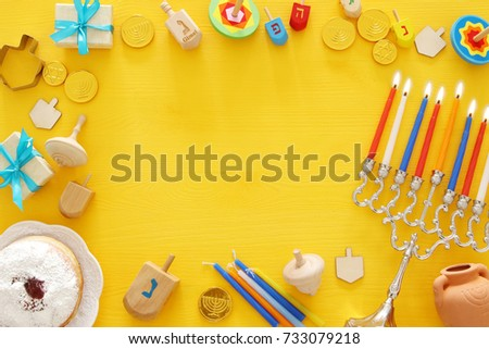 Top view image of jewish holiday Hanukkah background with traditional spinnig top, menorah (traditional candelabra) and burning candles