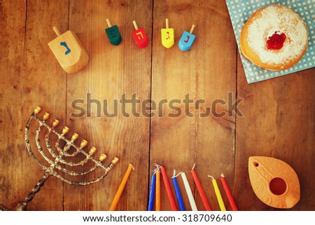 top view image of jewish holiday Hanukkah with menorah (traditional Candelabra), donuts and wooden dreidels (spinning top). retro filtered image