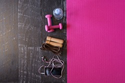 Top view image of jumping rope, smart phone, pink yoga mat and weights with a bottle of water on black wooden floor background. Equipment for fitness. Concept healthy lifestyle. Lots of copy space.