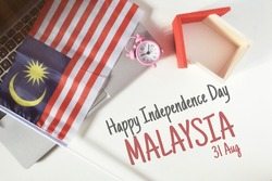 Top view image of Malaysia flag and house figure with Happy Independence Day Malaysia wording