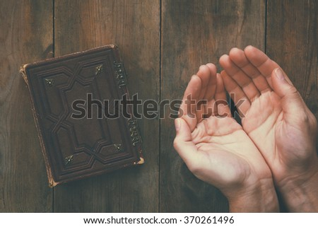 top view image of mans hands folded in prayer next to prayer book. concept for religion, spirituality and faith. vintage filtered and toned