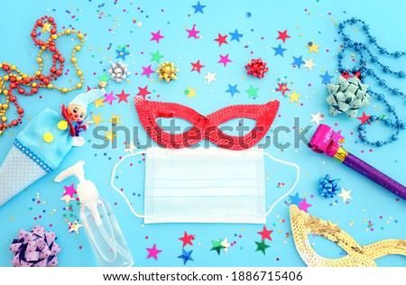 Top view image of masquerade mask background. Flat lay. Purim celebration (jewish carnival holiday). Coronavirus prevention concept, medical mask and sanitizer gel