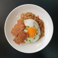Top view image of sunnyside up fried egg and luncheon meat on instant noodles. Home cook Asian food. Hong Kong breakfast.