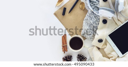 top view image of tablet computer, coffee and scarf background on white table. over light