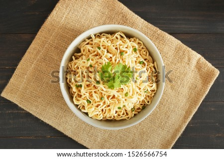 top view instant noodles in the bowl on wooden table background