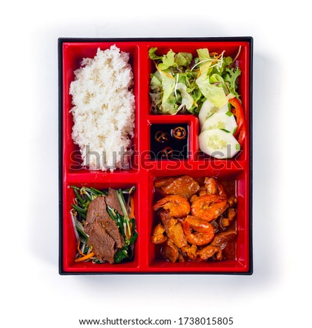 Top view Japanese Bento Box with shrimp, stir fried beef, salad and cucumber. Bento box isolated on white background