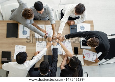 Top view join hands on work table of team of Asian people and foreigners at meeting. Hands coming together of teamwork. Concept of teamwork.
