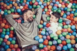Top view. Joyfull dad and son in pool with balls watching each other. Rest, holiday, leisure. Spending time together. Entertainment center, mall, amusement park.