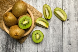 top view kiwi fruits on bowl with slices on wooden table