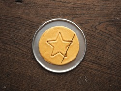 Top view Korean Dalgona or Ppopgi honeycomb sugar candy with star shape and needle on round tin tray on wooden background