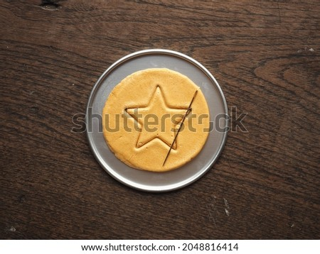 Top view Korean Dalgona or Ppopgi honeycomb sugar candy with star shape and needle on round tin tray on wooden background ストックフォト ©