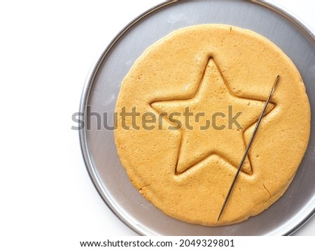 Top view Korean Dalgona or Ppopgi honeycomb sugar candy with star shape on white background