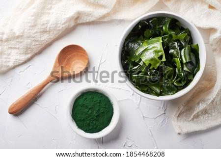 Top view laminaria or kelp seaweed and spirulina powder in white bowl and spoon background. flat lay spirulina powder with konbu and alga food on white background.