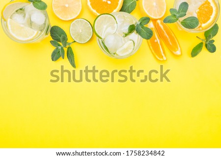 Top view lemonade set. Lemonade, mojito and orange lemonade. Iced summer drink with ingredients on yellow background. Flat lay and copy space