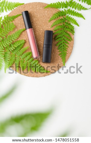 Top view liquid matt lipstick with applicator. Lipstick in a black tube. Lipsticks on cork mat with fern leaves on white. Copy space #1478051558
