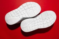 top view macro raised sole with treads on white running shoes with hard shadows isolated on a red background, sneakers with soles up.