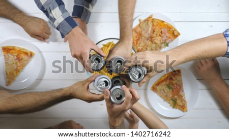 Top view male and female hands opening and clicking aluminum cans with soda on wooden table background. Group of best friends sitting at the desk and toasting together with cola indoor. Slow motion #1402716242