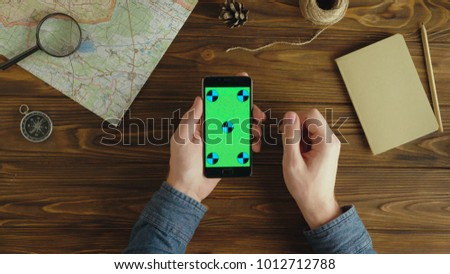 Top view. Man traveler hands using smart phone with green screen. Planning holidays. Chroma key. tracking motion #1012712788