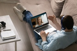 Top view man wearing headphones chatting with woman online, sitting on couch with laptop on laps, enjoying leisure time, boyfriend talking with girlfriend by video call, using social media app