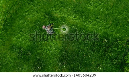 Top view man worker cutting grass with lawn mower.  #1403604239