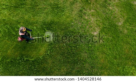 Top view man worker cutting grass with lawn mower.  #1404528146