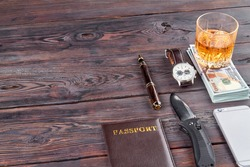 Top view mens accessories on wooden table. Passport with knife and pen.