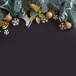 Top view Merry Christmas black background decorated with Happy New Year Christmas tree branches, snowflackes, bells and baubles with copy space