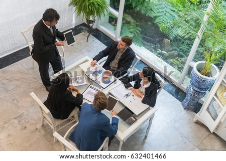 Top view Middle-aged businessman is presenting to a group of business people meeting.