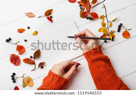 Top view mock up woman hands with notebook on wthite wooden background with autumn leaves. 'To do' list for autumn. Planning of autumn walk route, to-do list or shopping. Relax, wish list, play list