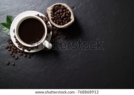 Shutterstock Top view mockup a cup of coffee with coffee beans and leaves on the black stone.
