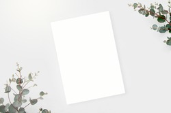 Top view mockup blank card, for greeting, wedding invitation template with eucalyptus leaves on white background.
