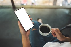 Top view mockup image of a woman holding a black mobile phone with blank white desktop screen with coffee cup