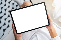 Top view mockup image of a woman holding black tablet pc with blank white desktop screen while sitting in bedroom with feeling relaxed in the morning