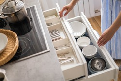 Top view modern housewife tidying up kitchen cupboard during general cleaning or tidying up. Female neatly placing dishware and cutlery in drawer of table. Storage organization Konmati method