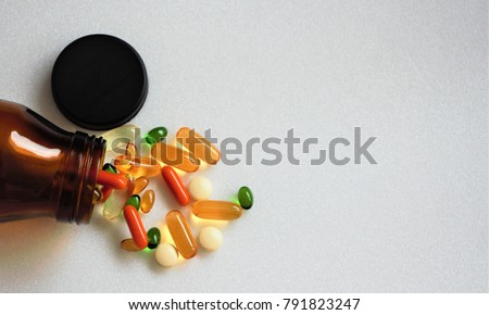 Top view multi vitamins and supplements with brown bottle on white background with copy space.