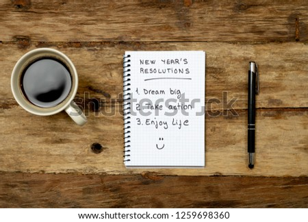 Top View 2019 New year resolutions list with plans for new life happy face written on notepad coffee and pen on Vintage table in Dreams and Goals for happiness Aspiration and Motivation Concept. #1259698360