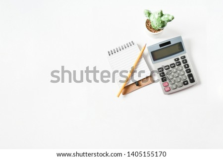 Top view objects yellow pen on small notebook  , small cearamic cactus green ,calculation and on white background isolated, idea home loan background or home finance concept. sensitive focus.