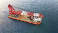 Top view of a barge equipped with a powerful crane currently in rest position for a transit. Oil and Gas, Construction, heavy lift background.