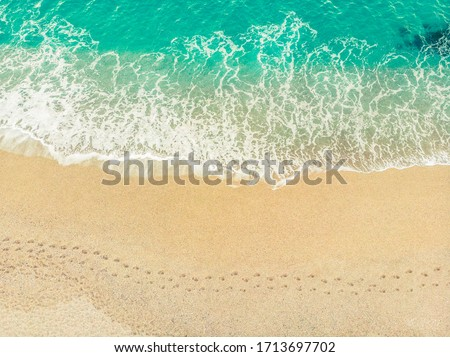 Top view of a beach with barefoot walk marks along