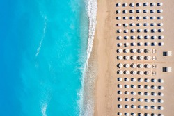 Top view of a beach with symmetrical sunbeds and parasols next to turquoise sea as seen in Greece