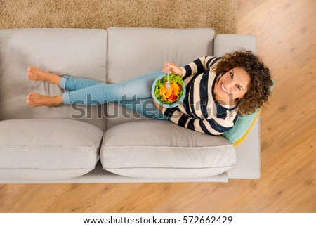 Top view of a beautiful woman on the sofa eating a healthy salade