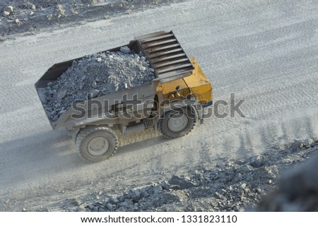 Top view of a big mining dumping truck transporting stone ore on the road in a stone quarry, close-up.