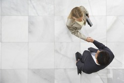 Top view of a businessman and woman shaking hands in office lobby