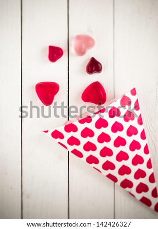 Top view of a candy cone decorated with pink hearts spilling heart shaped gummy candies over a white wooden board table
